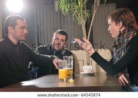 Two young mans and girl in a cafe - stock photo