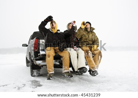 Two young men and a young woman drinking beer while sitting on the tailgate of a truck in a winter environment. Horizontal shot.