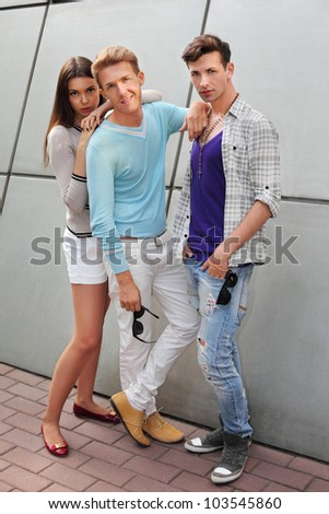 Two young men and beautiful woman stand near gray wall; good friends