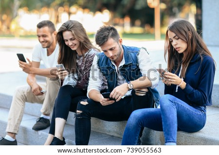 Two young men and women use telephone sitting on stairs outdoors. Friends communicate, exchange photos, chatting in social networks. Dependence on smartphone, modern technology in people lives concept