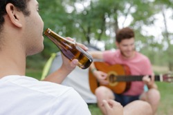 two young men by tent playing guitar and drinking beer