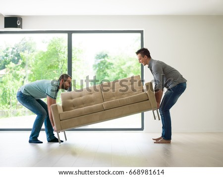 two young men carry the sofa in front of window
