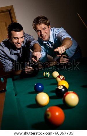 Two young men discussing snooker game, having beer, pointing at balls on table, smiling.?