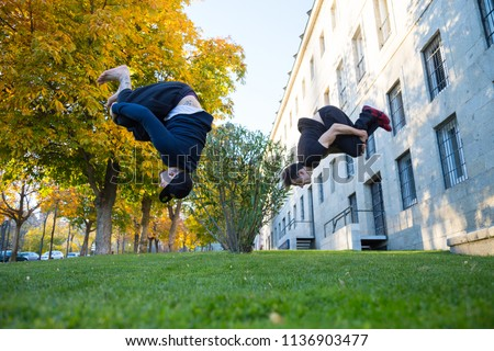 Two young men doing a side flip or somersault while they practicing parkour on the street.  #1136903477
