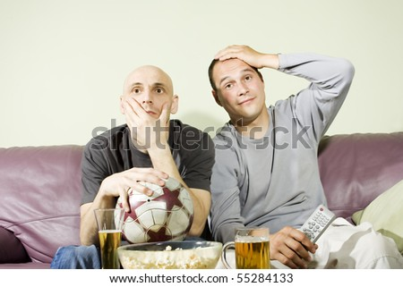 Two young men drinking beer at home and watching soccer on tv