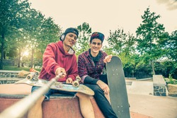 Two young men in a skate park holding a selfie stick and photographing themselves - Two skaters having fun on a skate competition