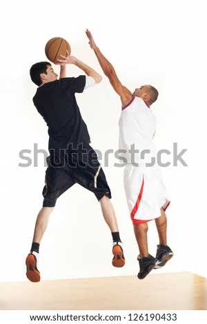Two young men in basketball uniform playing basketball on white background.