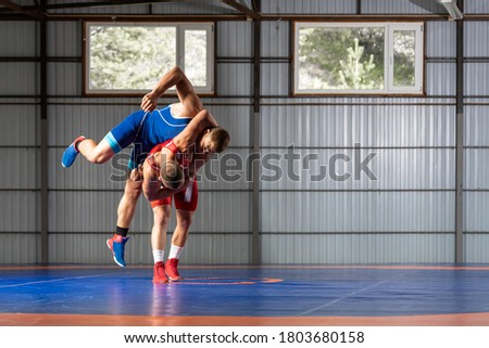 Two young men in blue and red wrestling tights are wrestlng and making a thigh throw, wrestling on a blue wrestling carpet in the gym. The concept of fair wrestling