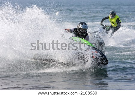 Two young men or teenagers speeding towards a marker buoy on a small jetbike or jetski during a race on the sea or ocean