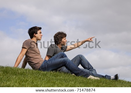 Two young men sited on the grass looking and pointing away