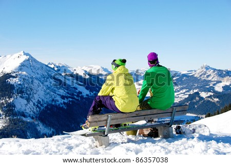 Two young men sitting on a bench on top of a mountain. They are having a break after snowboarding the snowy Alps