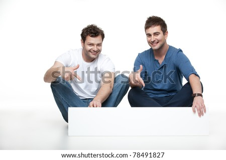 two young men sitting pointing blank banner
