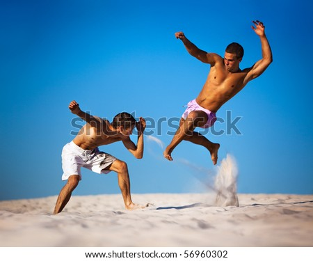 two young men sport fighting on beach stock photo