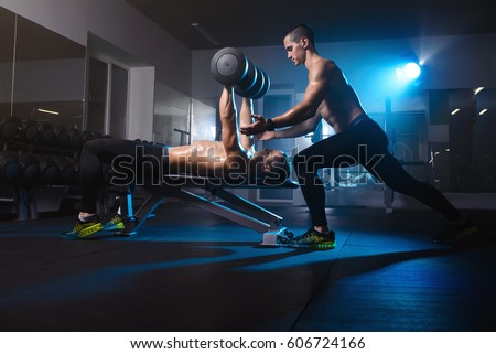 two young men twin brothers training with dumbbells, exercising workout in gym