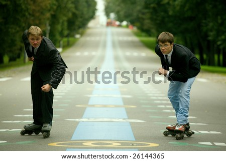 Two young men wearing rollerblades are skating on the road.
