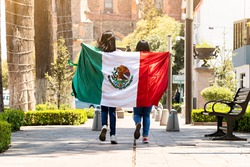 two young mexican women running on a walkway on a tree-lined street, with the mexican flag