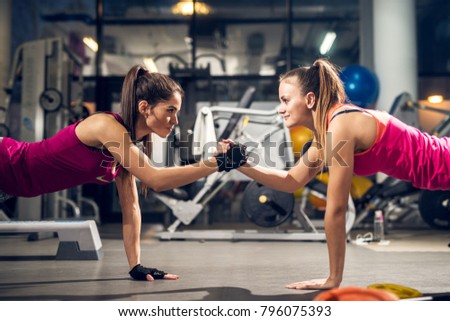 Two young motivated aggressive attractive focused sporty active girls doing push ups and holding hands together while looking each other in the modern gym.