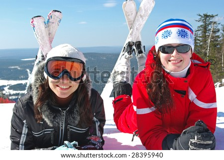 Two young mountain-skiers resting on the slope.