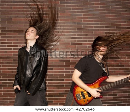 Two young musician jumping against brick wall