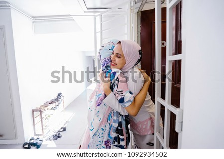 Two young Muslim women embrace as one welcomes her into her home to celebrate Hari Raya together.  #1092934502