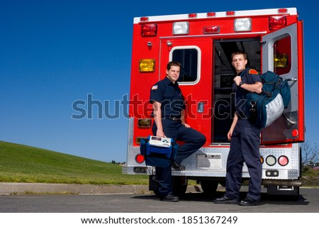 Two young paramedics carrying medical equipment standing in front of an open ambulance door on a bright, sunny day Photo stock ©