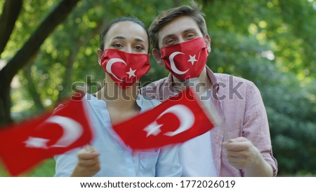 Two young people are waving the Turkish flag while looking at the camera. They wear a medical mask in the form of a Turkish flag to protect them from the virus. Stock fotó ©