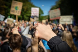 two young people at a rally, joining hands together signaling peace, unity and decisiveness in front of a crowd carrying protest placards with shallow depth of field