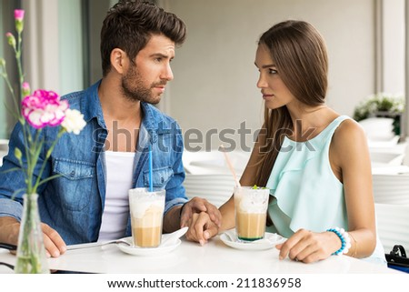 Two young people drinking frappe in restaurant