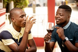 Two young people enjoying wine at the restaurant. Tasting of elite drinks. Verification of taste, color, sediment of wine. All happy man