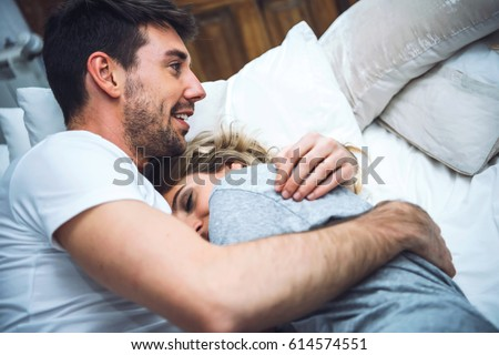 Two young people in pajamas cuddling together in bed.