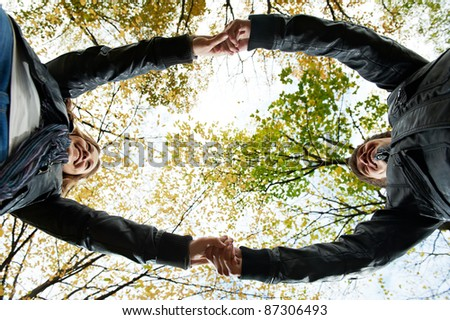 Two young people join hands in park at autumn outdoors date. Girl wear chaplet from maple