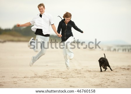 two young people jumping on the beach  and holding tight - stock photo