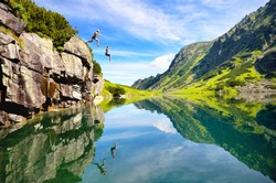 two young people jumping to the water in beautiful mountains nature. Fresh and free scenery from summer vacation