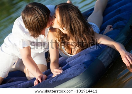 Two Young People Kissing On The Swimming Mattress Stock ...