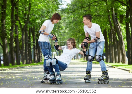 Two young people lift the fallen girl on rollers