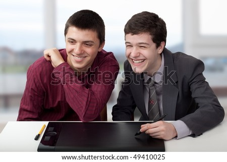 Two young people looking about some project and having fun time