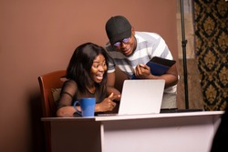 two young people looking into a laptop