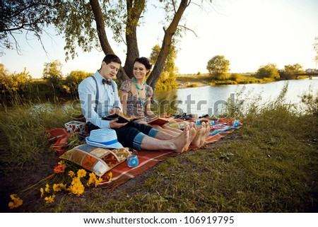 two young  people reading books at the park
