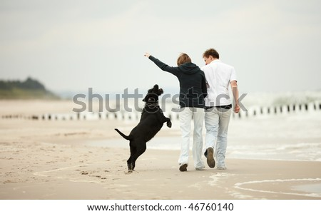 two young people running on the beach kissing and holding tight with dog