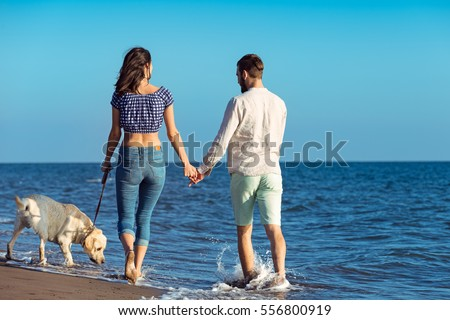two young people running on the beach kissing and holding tight with dog #556800919