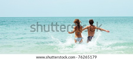 Two young people running to the blue sea