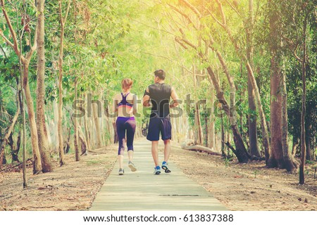 two young people running together on road. Man and woman jogging outdoors. #613837388