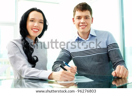Two young people signing a contract and looking at camera with a smile