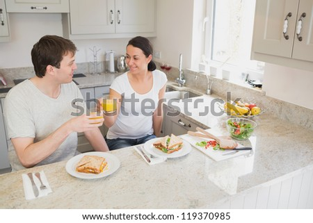 Two young people sitting in the kitchen and having a healthy meal