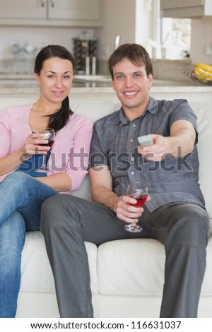 Two young people sitting in the living room while watching television - stock photo