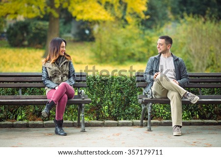 Shutterstock Two young people sitting on benches in a park and talking