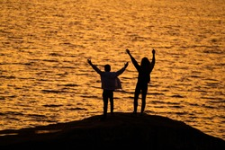 Two young people standing on rock in front of water with hands up looking at sundown. silhuette against sunset
