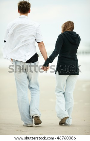 people walking on the beach. stock photo : two young people