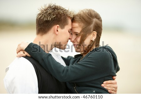 Two Young People Walking On The Beach Kissing And Holding ...