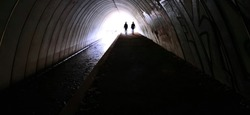 Two young people walking through a dark tunnel towards the bright light at the end